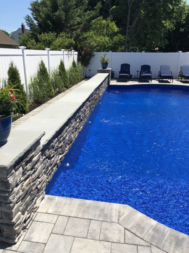 gray pool with blue stone rock face and grey stone veneer